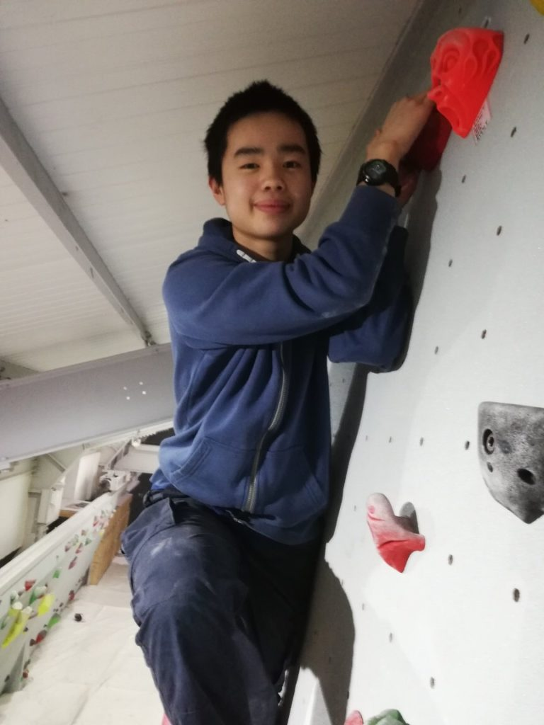 An image of Josh on a climbing wall